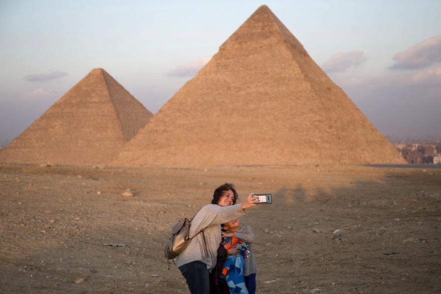 Γυναίκα με παιδί βγάζουν φωτογραφία μπροστά στις Πυραμίδες της Αιγύπτου