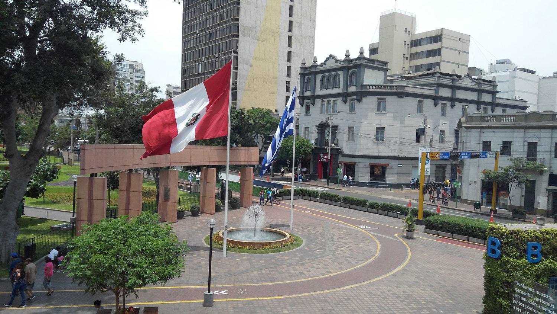 Η ελληνική και περουβιανή σημαία κυματίζουν στην είσοδο του πάρκου Kennedy μπροστά από το Δημαρχείο της Miraflores