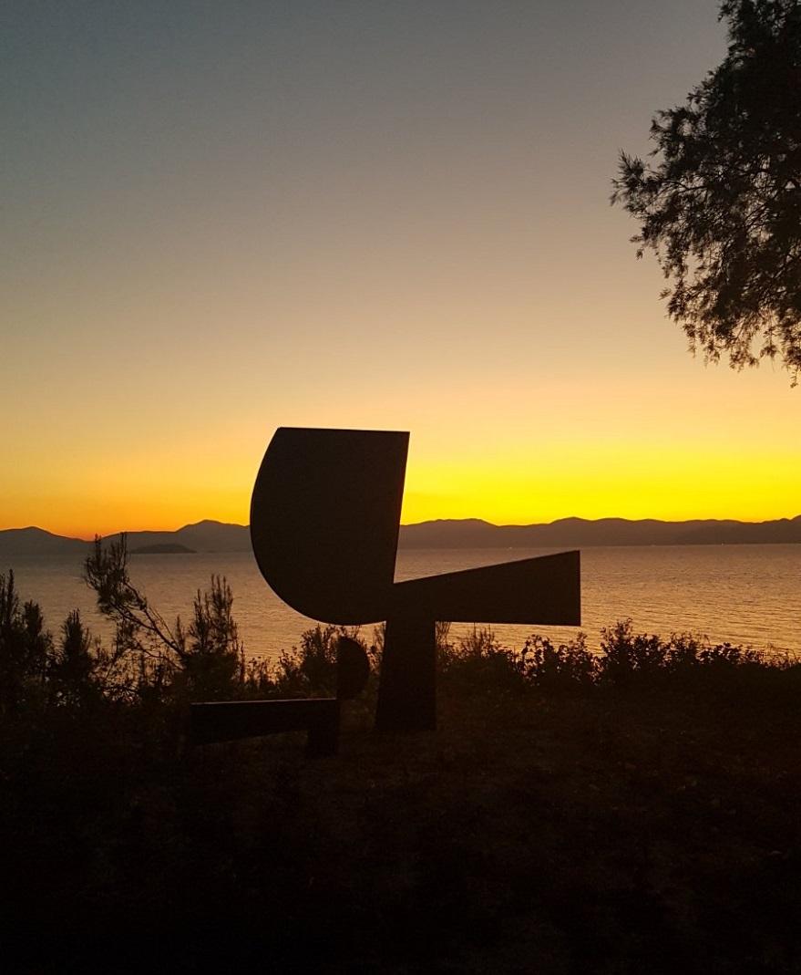 Γλυπτό του Γιάννη Μώραλη στην Αίγινα με φόντο το ηλιοβασίλεμα
