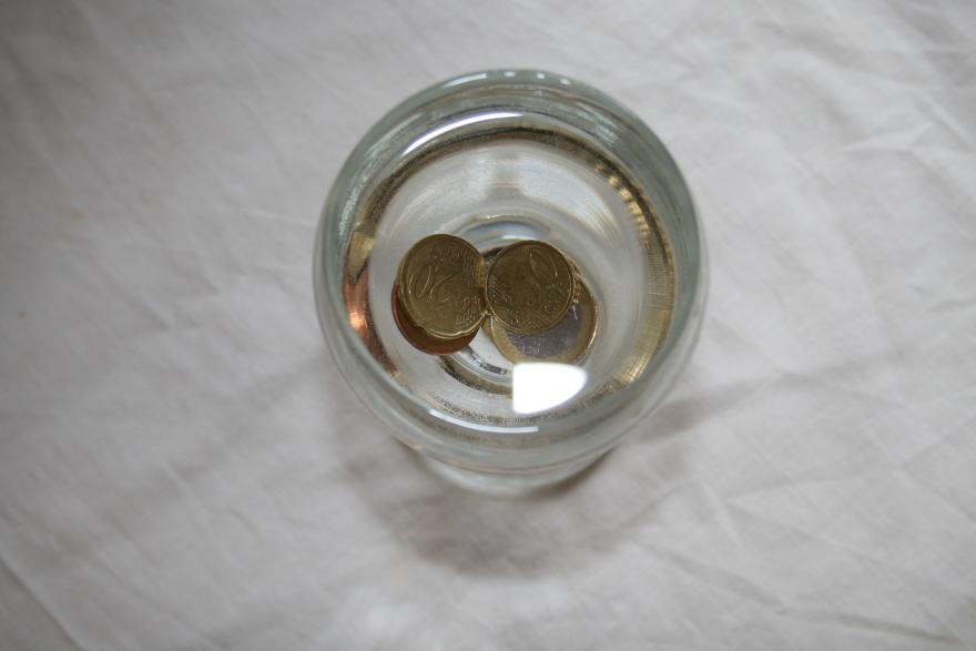 Κέρματα σε ποτήρι μισογεμάτο με νερό