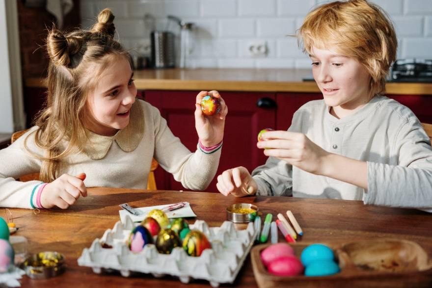 Παιδιά στην κουζίνα βάφουν πασχαλινά αυγά
